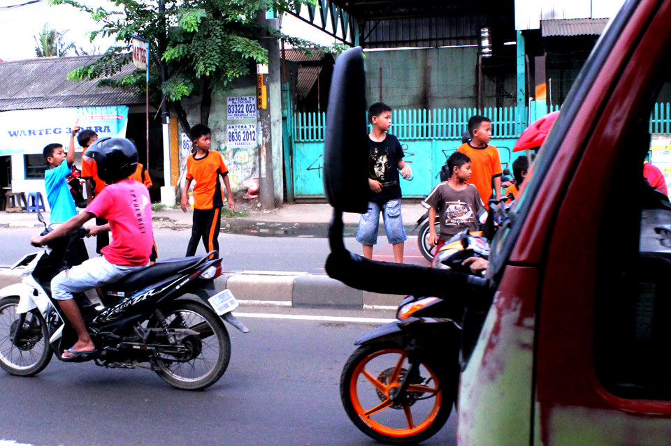 Sambil berjalan di tembok pembatas jalan, para remaja ini sering melihat ke belakang. Menunggu truk yangakan mereka tumpangi.