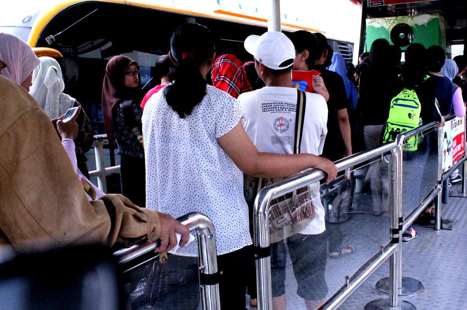 Bus Transjakarta yang tak sanggup menampung  semua penumpang yang antri di ruang tunggu