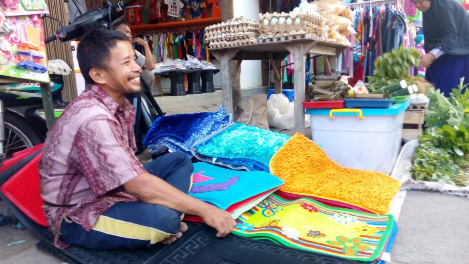 Indra yang selalu senyum menyapa para pengunjung pasar tempat dia berdagang.