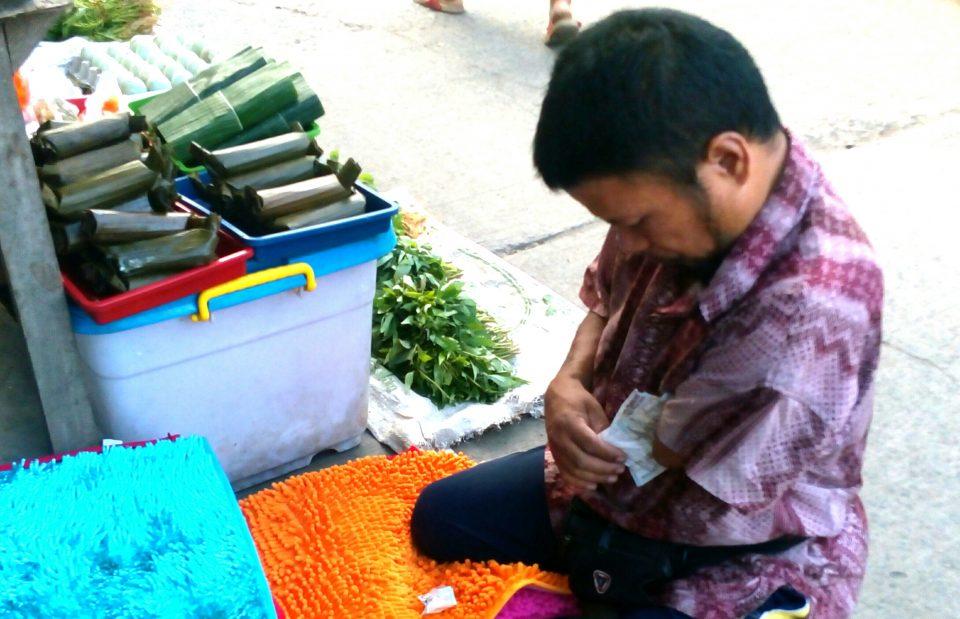 """Dengan bantuan """"tangan kiri""""nya Indra merapikan uang penjualan keset yang diterimanya dari pembeli."""